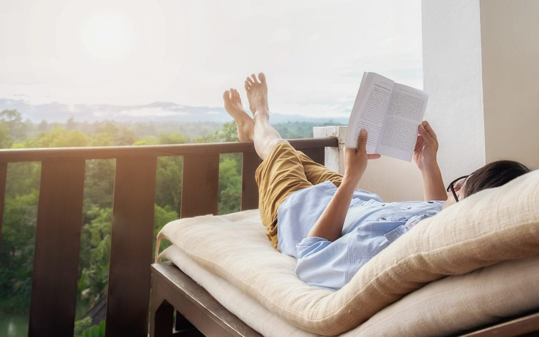 Why You Should Be An Advocate for Hearing Loss | Lady reading book with feet up on balcony | Physician Hearing Care Tennessee