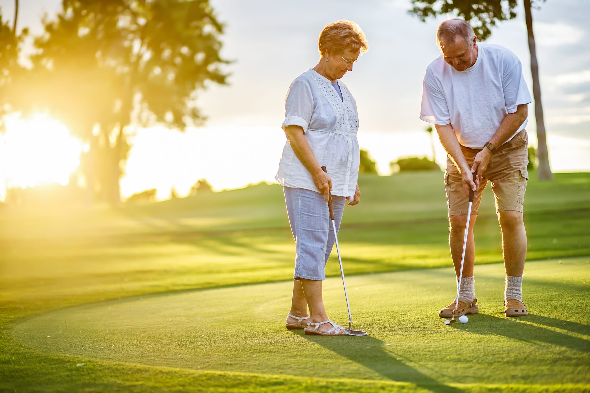 active senior lifestyle, elderly couple playing golf together at sunset | PHC Tennessee