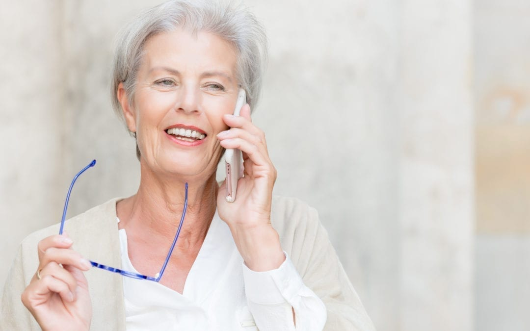 elderly lady holding glasses in her hand and talking on the phone