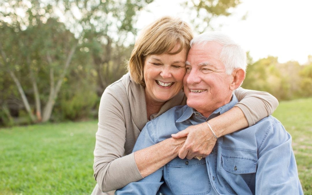 Elderly couple hugging and smiling in a park
