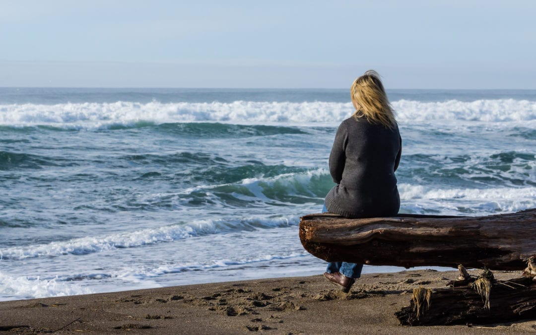 Woman sitting on a driftwood log | Scottsdale ENT