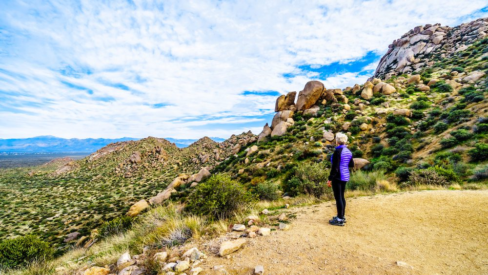 Senior woman hiker enjoying the view of the Valley of the Sun and the McDowell Mountain Range around Phoenix, Arizona viewed from the Tom's Thumb Trail | Scottsdale ENT