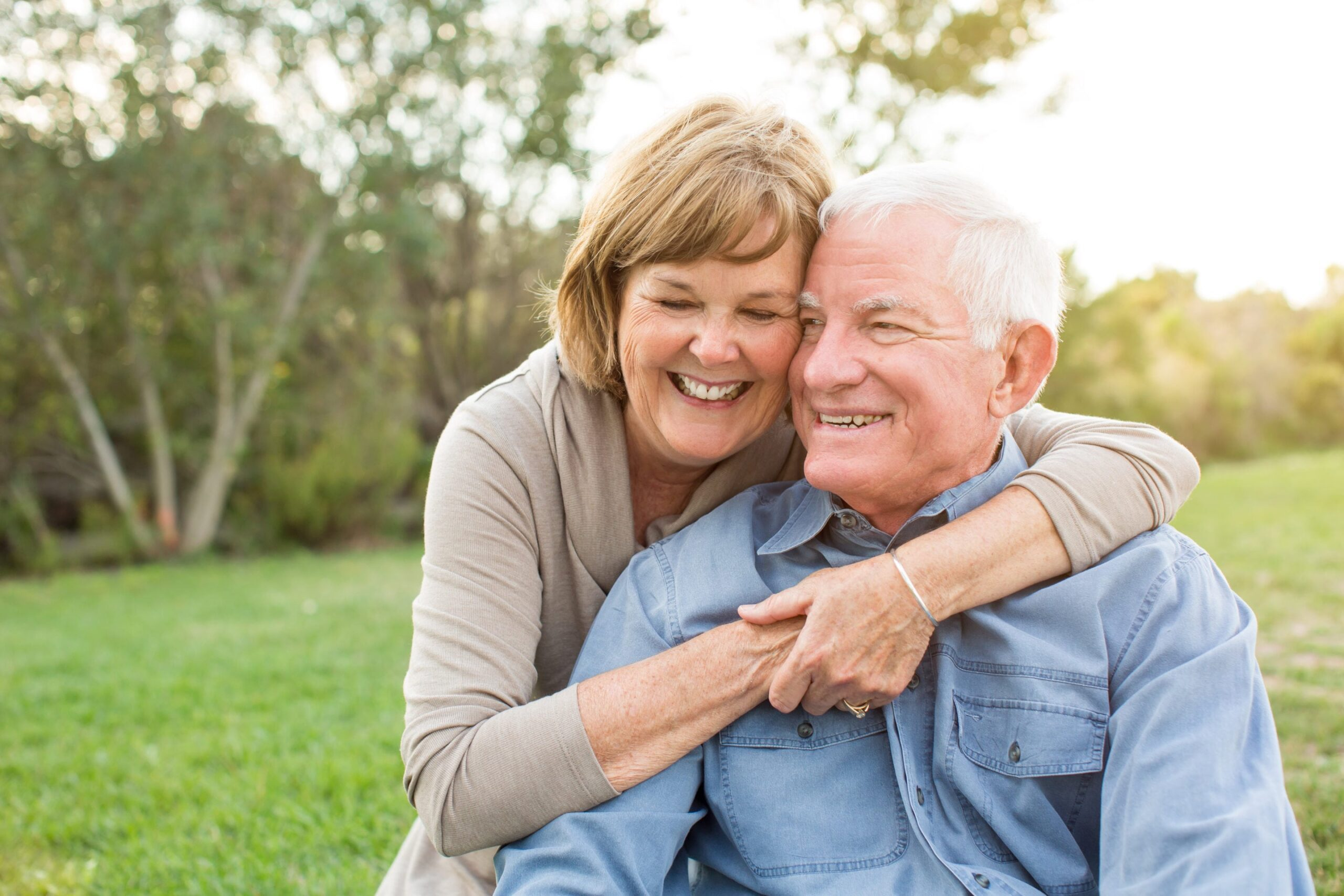 elderly couple hugging and smiling in park