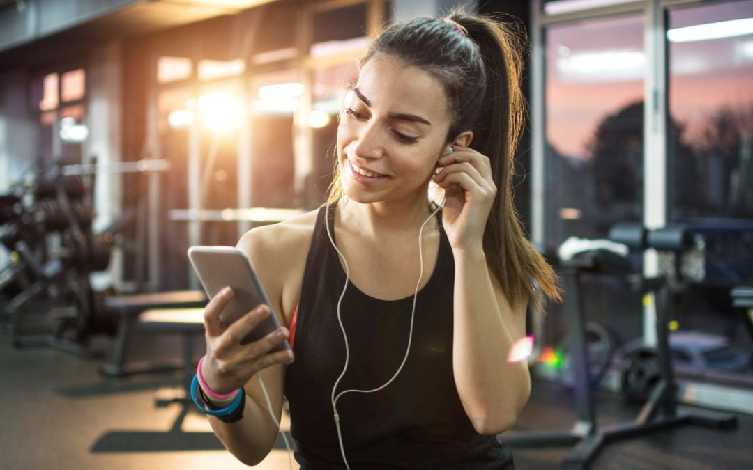 Lady listening to musci at the gym | Beltone Hearing