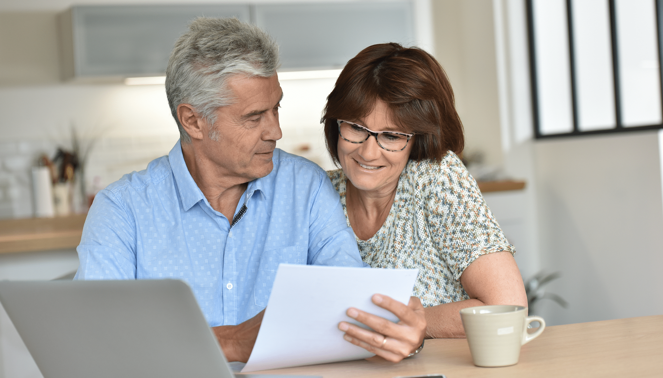 Couple sitting at table with laptop on looking at paperwork