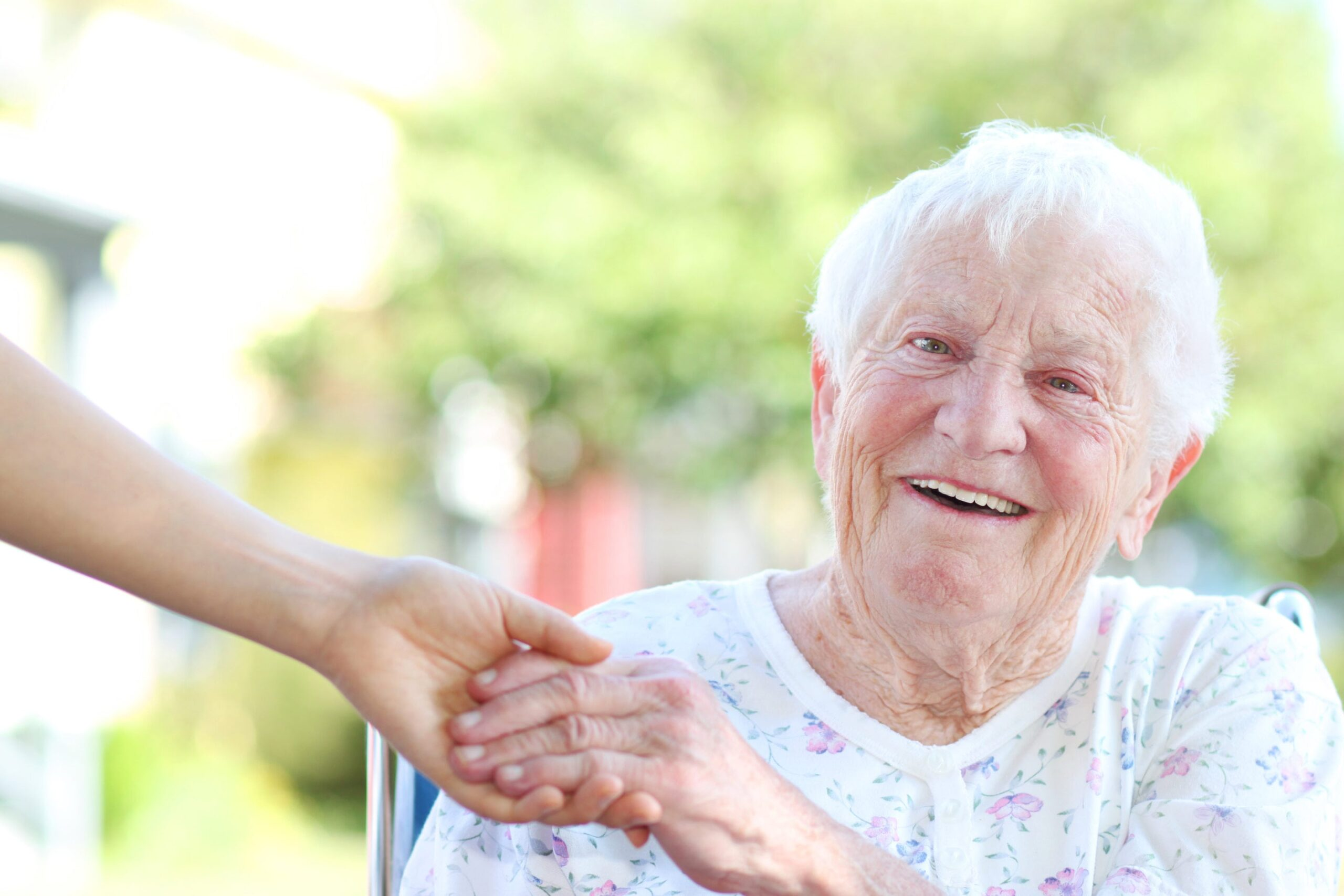 Senior lady smiling at camera and holding a younger lady's hand