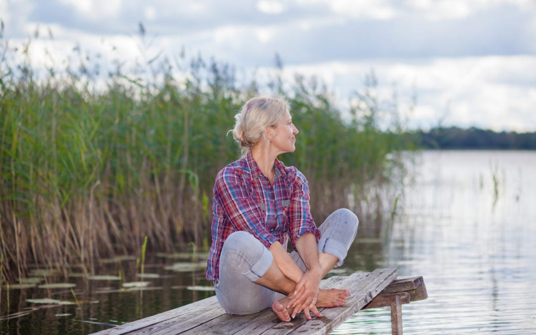 Middle aged woman relaxing on pier