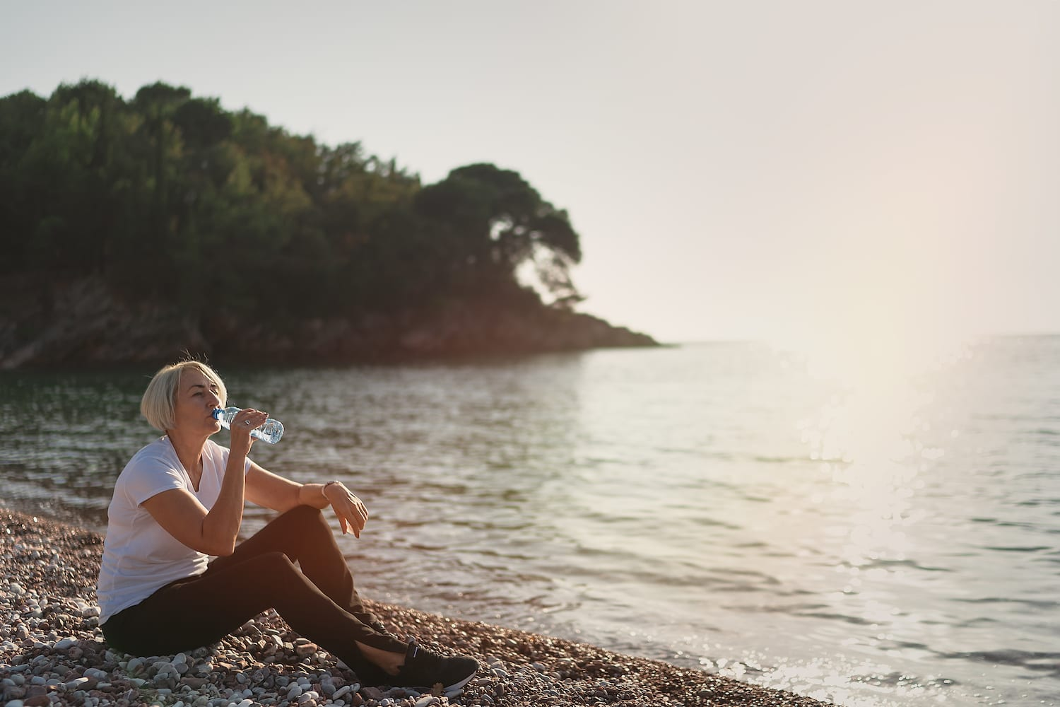 Mature woman drinking water during sunset after jogging. Senior lady sitting on the beach against the backdrop of the sea   Beltone Hearing