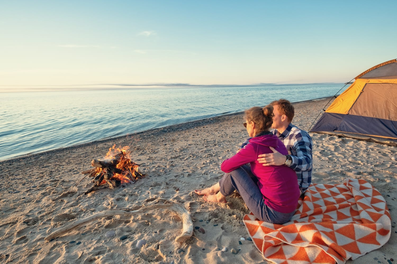 young couple on beach by fire camp enjoying sunset | Beltone Hearing Aid