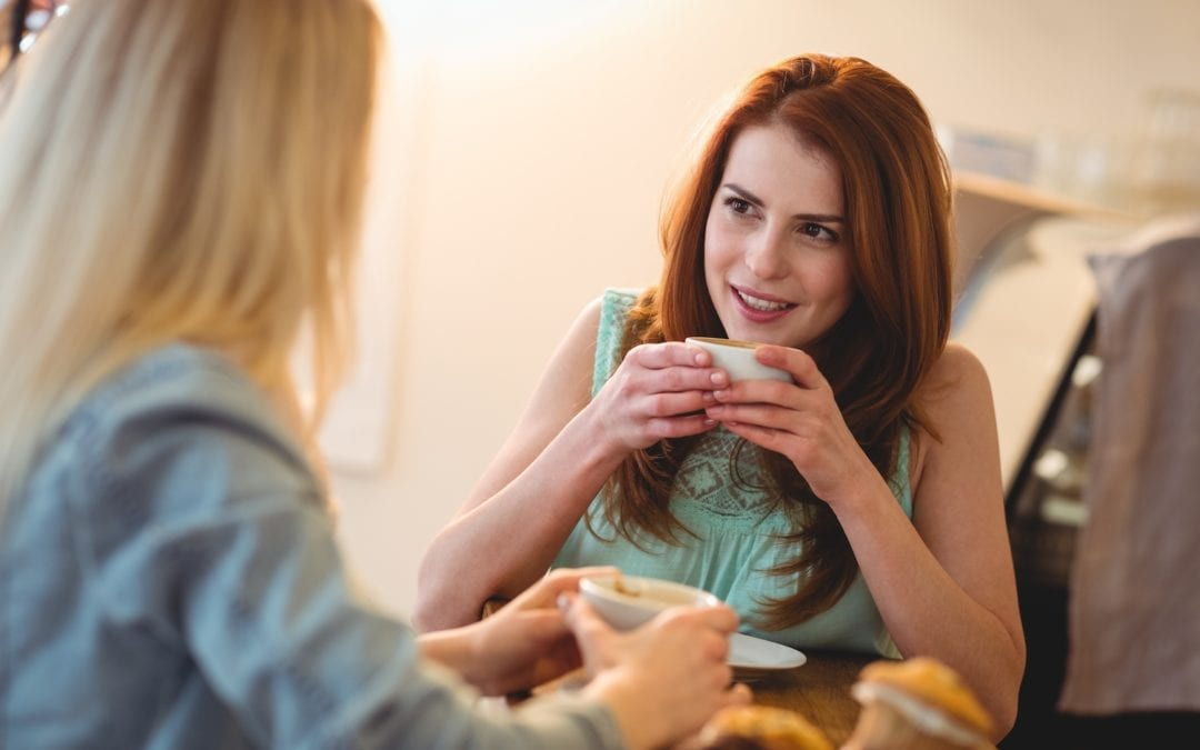 Happy woman listening to friend at coffee shop | Acadian Hearing