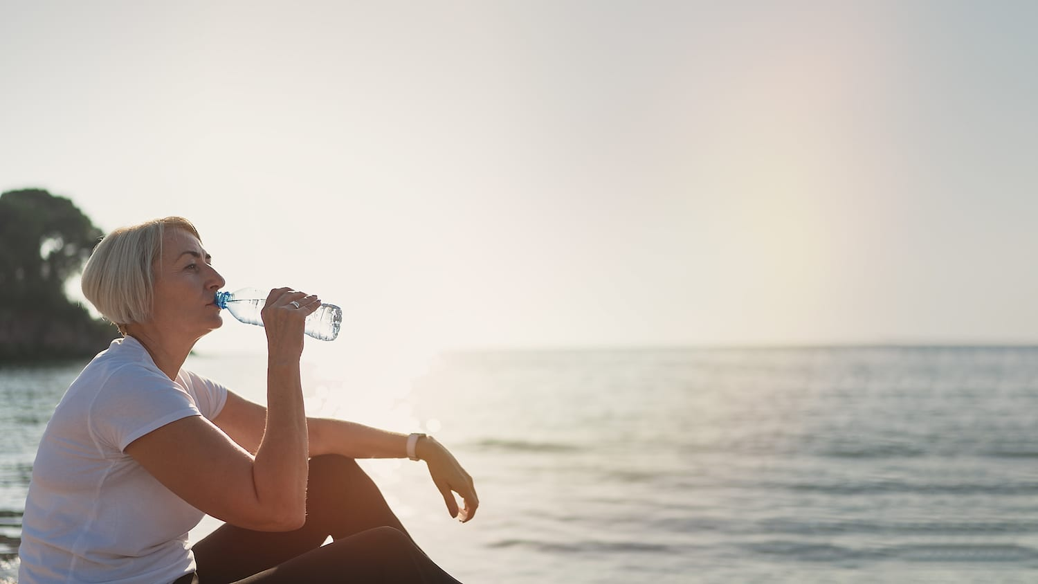 Mature woman drinking water during sunset after jogging. Senior lady sitting on the beach against the backdrop of the sea   Acadian Hearing
