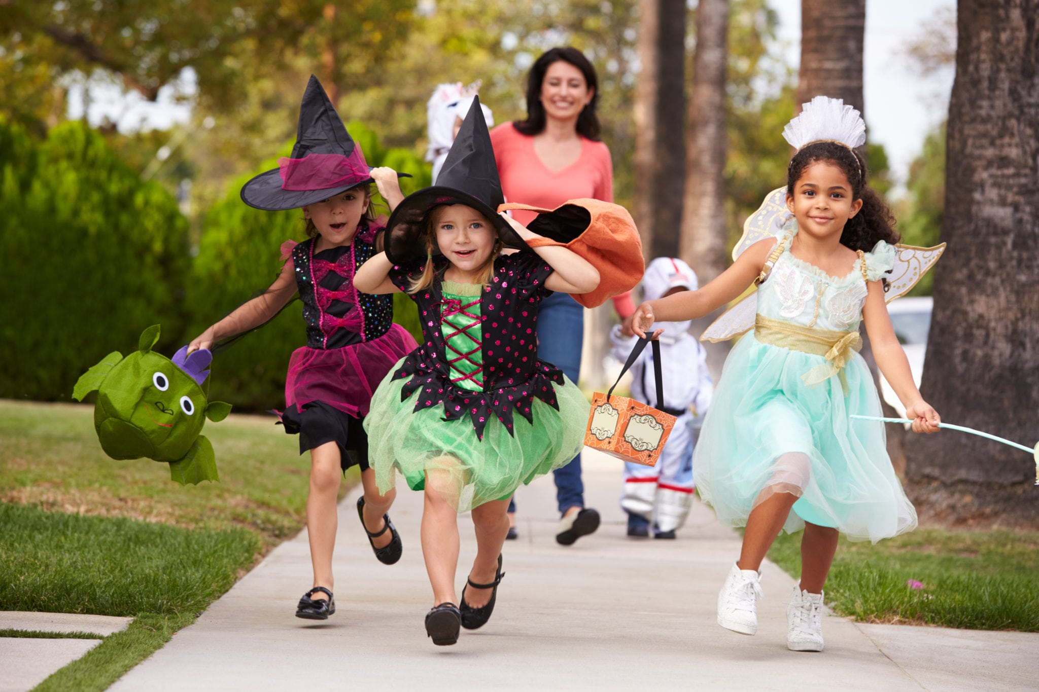 Parent Taking Children Trick Or Treating At Halloween | North Houston