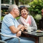 Senior couple in love sitting in street cafe, drinking coffee, talking, laughing and having fun. Happy people in retirement concept.   North houston