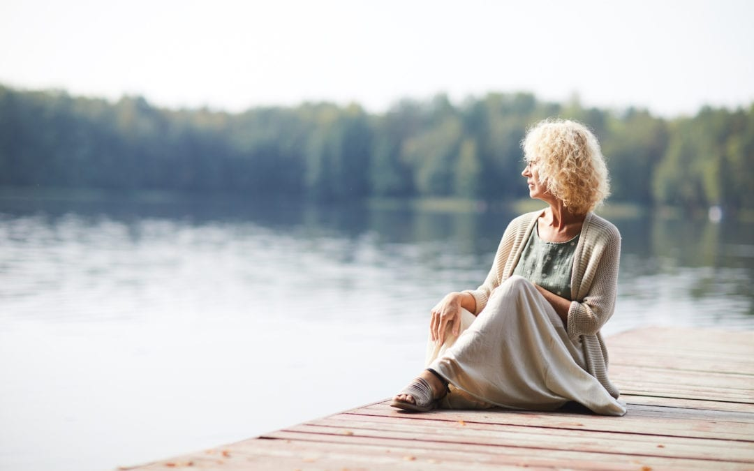 Pensive mature lady on pier | North Houston Hearing Solutions