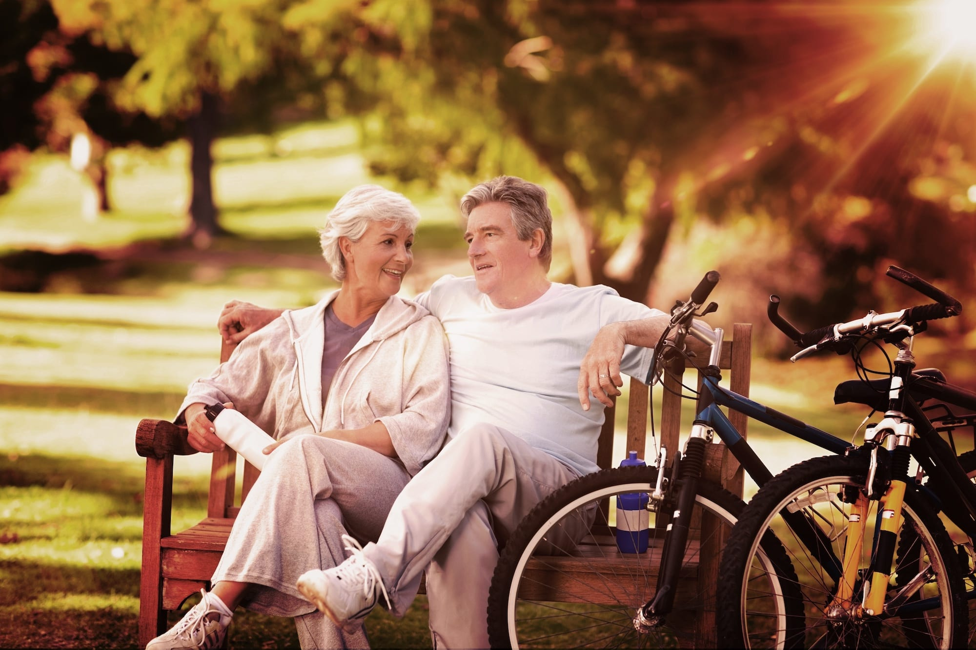 Composite image of elderly couple with their bikes |Slent Hearing & Balance