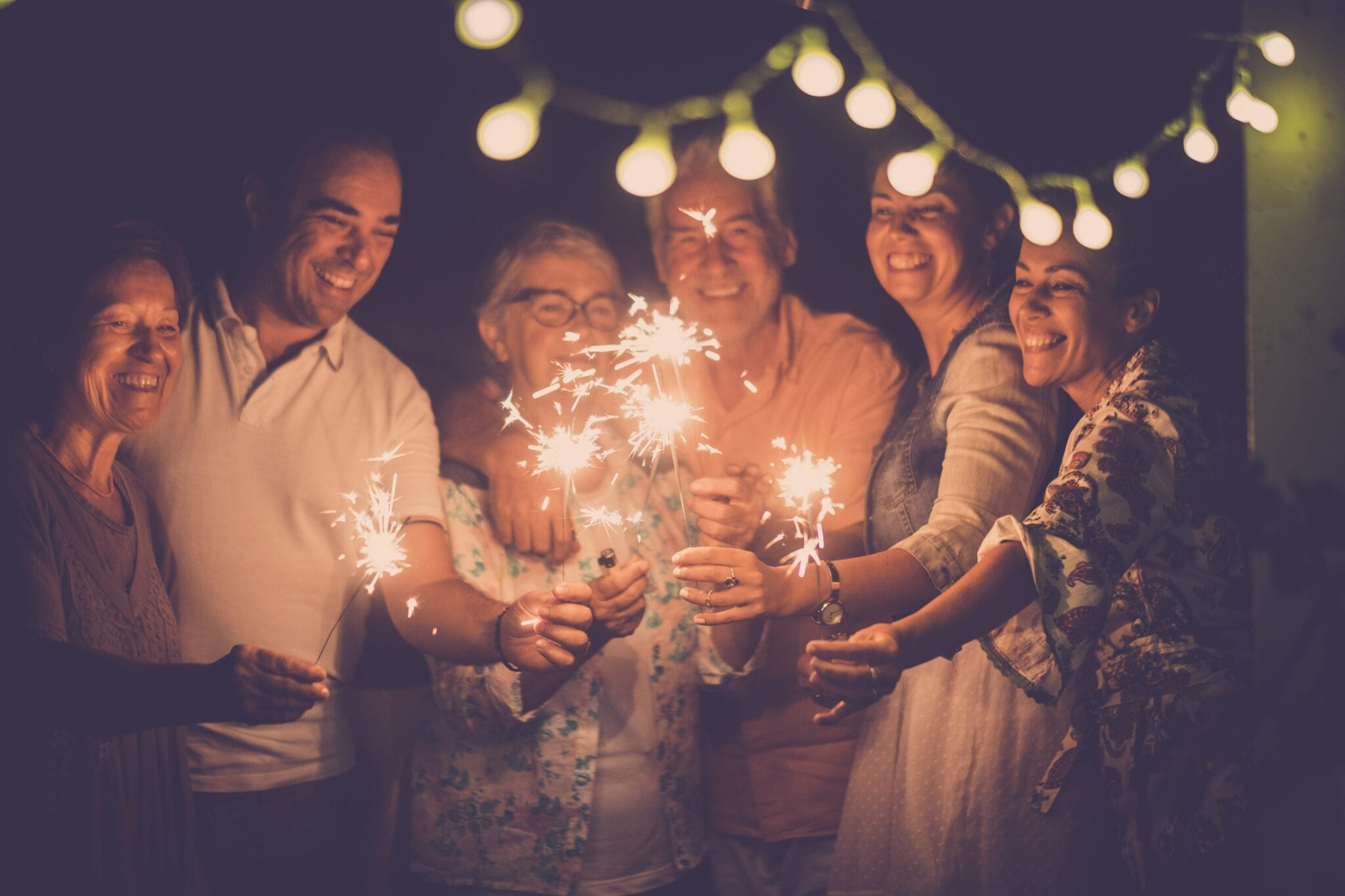 group of caucasian people friends with different ages celebrate together a birthday or new year eve by night outdoor at home. lights and sparkles with cheerful women and men having fun in friendship | Dr. michelle