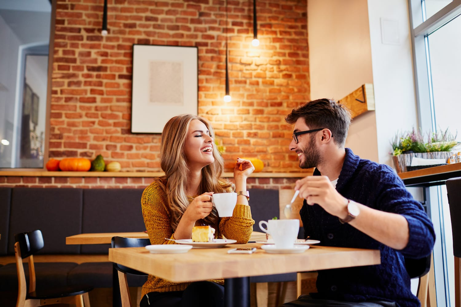 Couple of young people drinking coffee and eating cake in a stylish modern cafeteria | Dr. Michelle