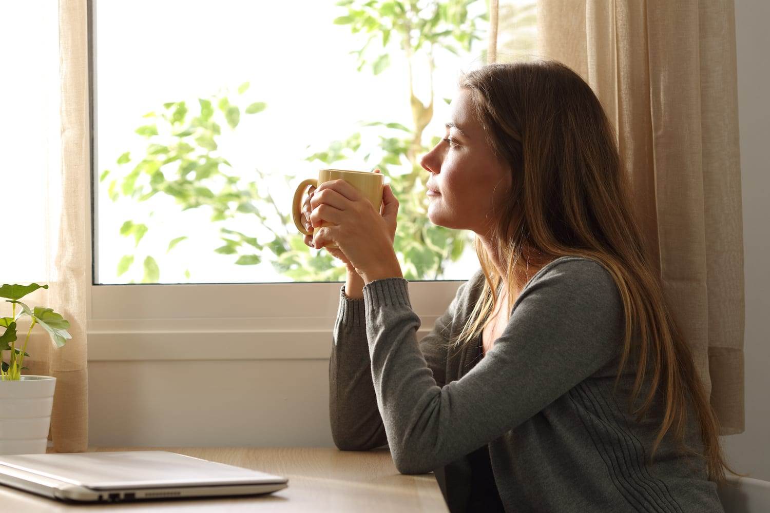 Relaxed woman looking through a window at home | Dr. Michelle