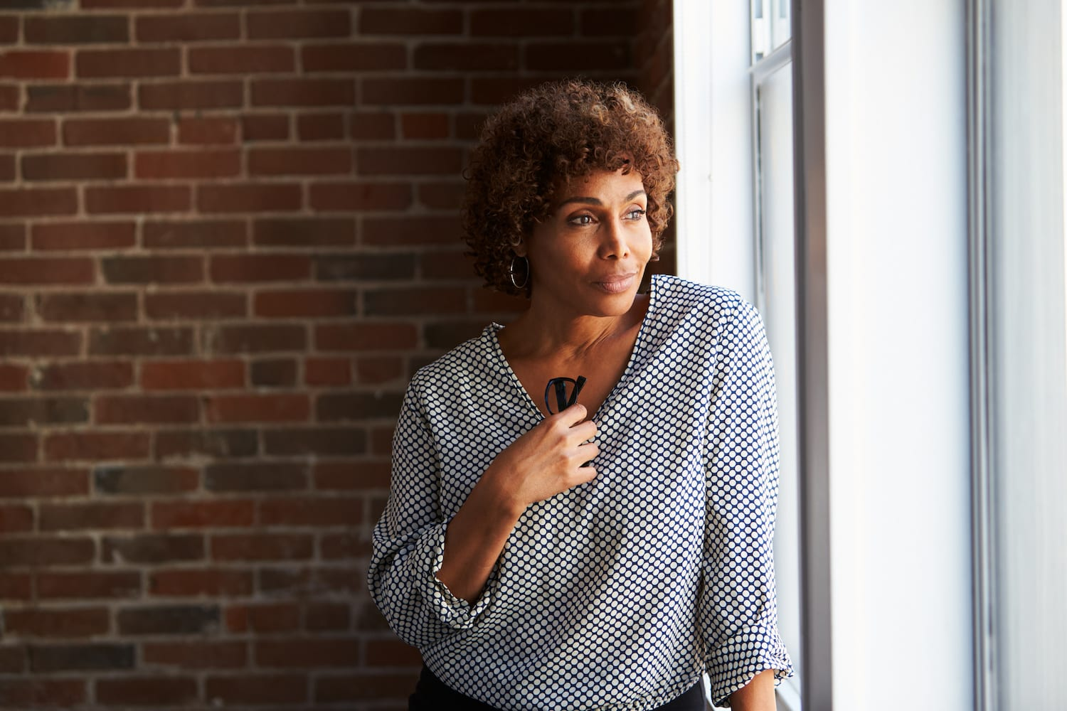Thoughtful Mature Businesswoman Looking Out Of Office Window | Dr. Michelle