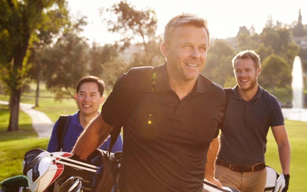 Group Of Male Golfers Walking Along Fairway Carrying Bags | Dr. Michelle