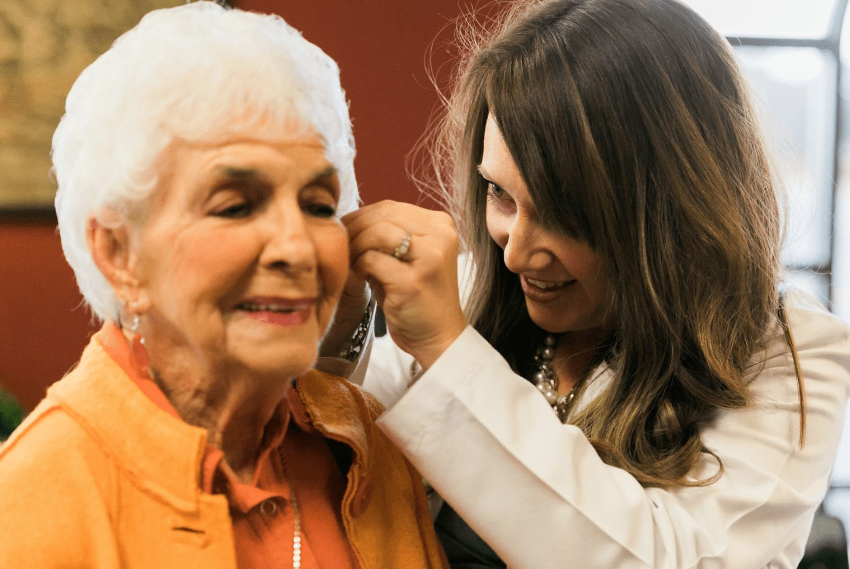 Dr. Julie Hubik adjusting hearing aids on happy elderly patient