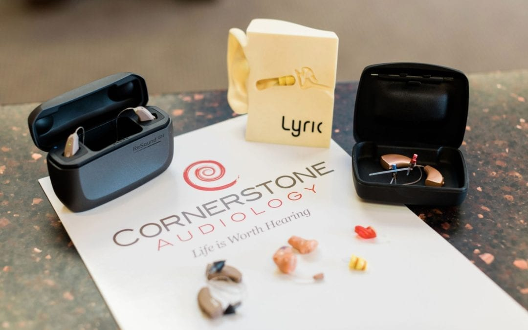 Lyric and ReSound hearing aids in protective boxes on table top