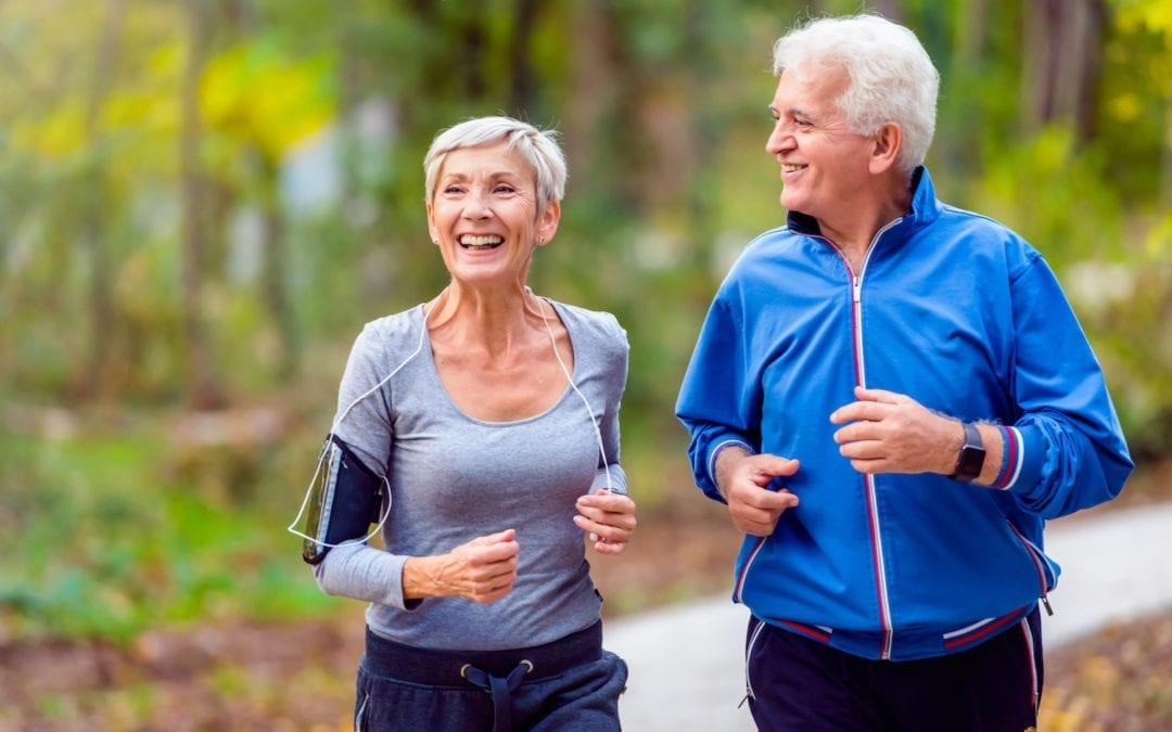 Elderly couple jogging through the woods while chatting and laughing