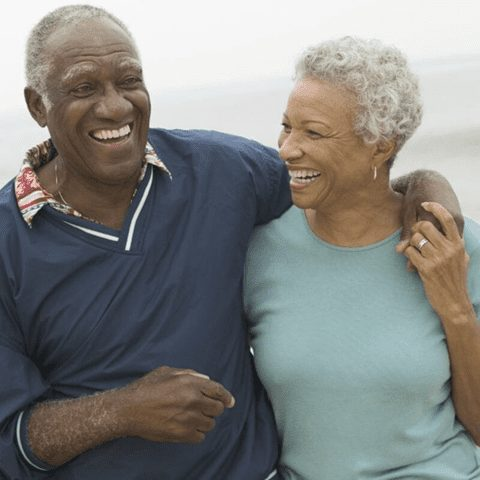Happy elderly couple walking with arms around each other
