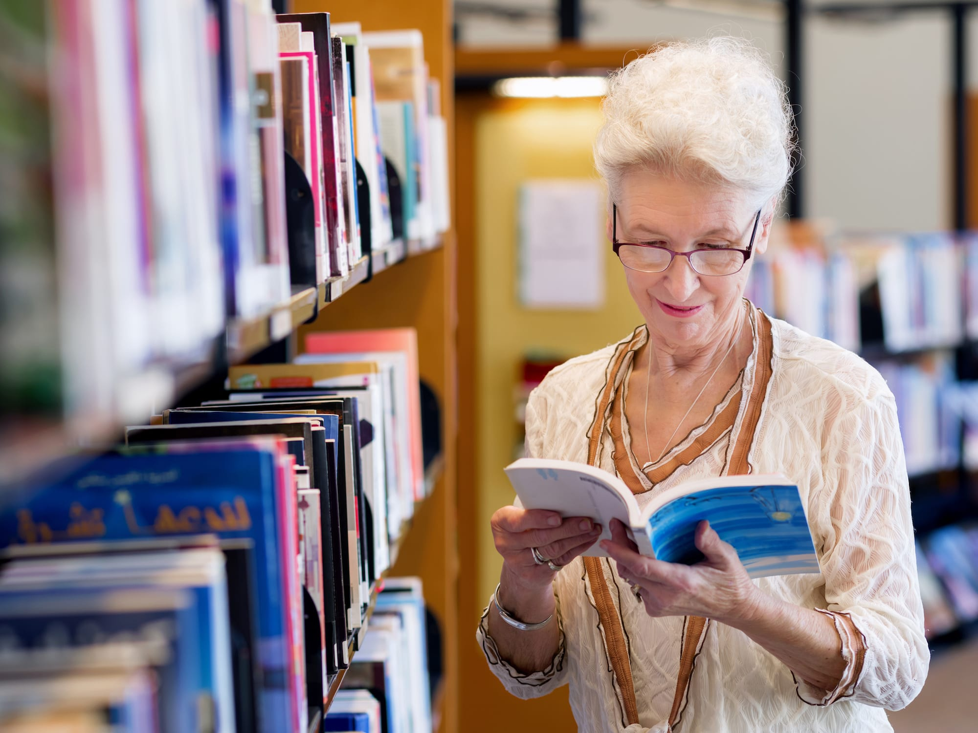 Elderly lady enjoying herself reading in library