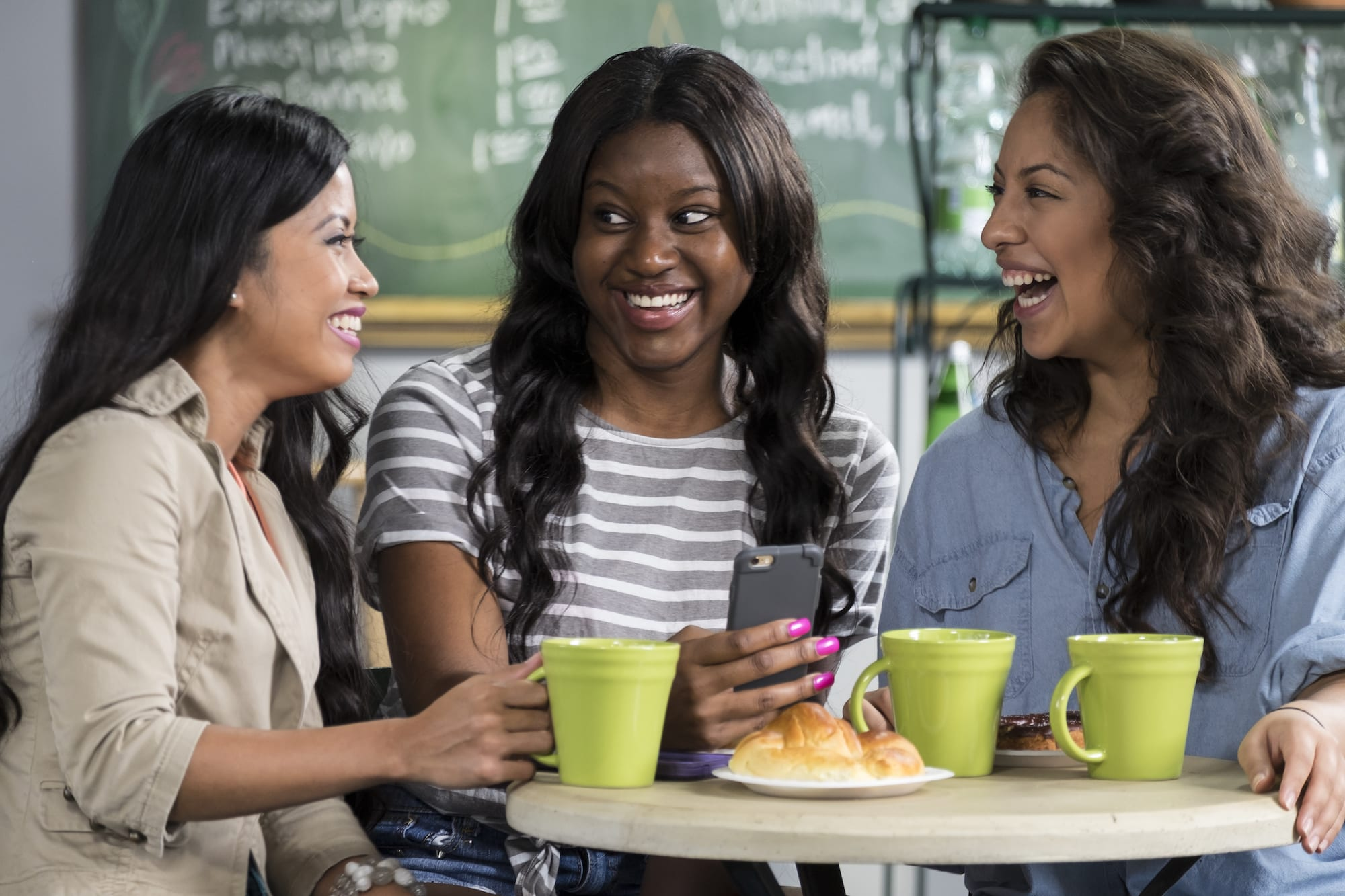 Three friends enjoying coffee in a cafe and laughing at a cellphone