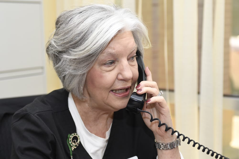 Aim Hearing & Audiology staff member S. Anne Hicks taking a phonecall in the office