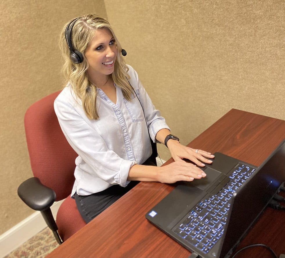 Kelsi sat at desk conducting teleaudiology appointment