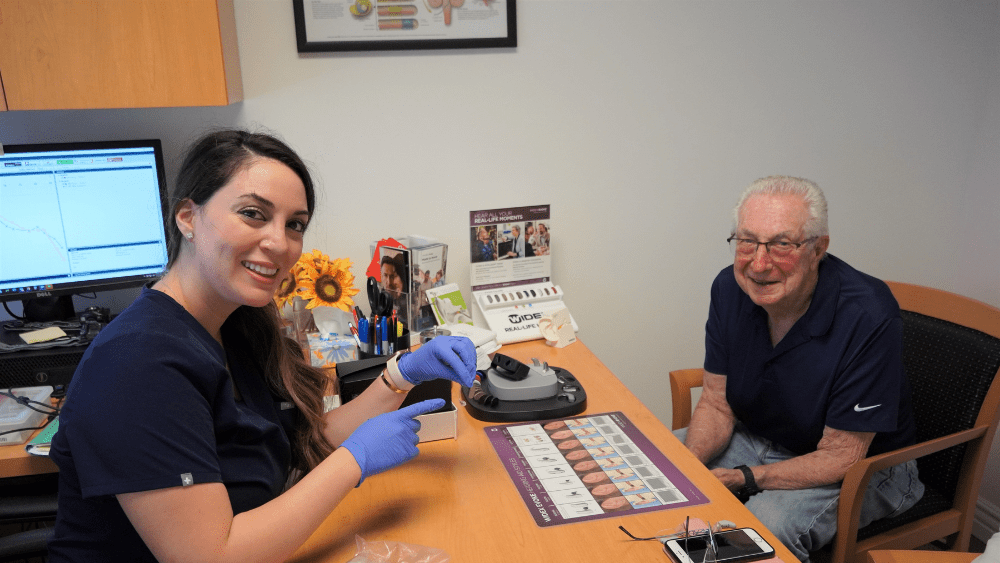 Audiologist and patient smiling into camera