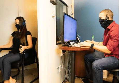 Lady sat in hearing test booth