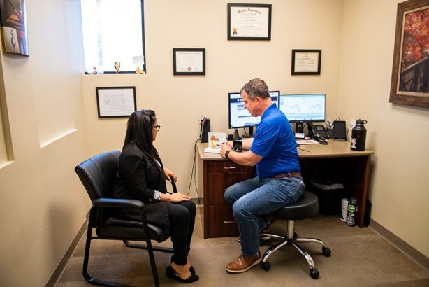 young woman being shown different hearing aid technology by audiologist