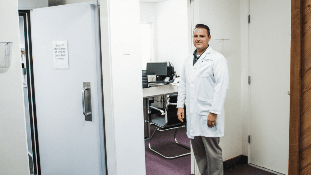 Audiologist stood outside assessment room smiling into camera