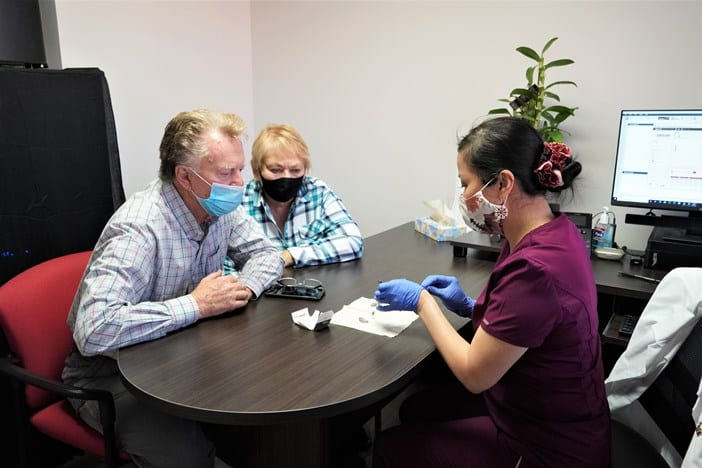 audiologist showing patient hearing aids