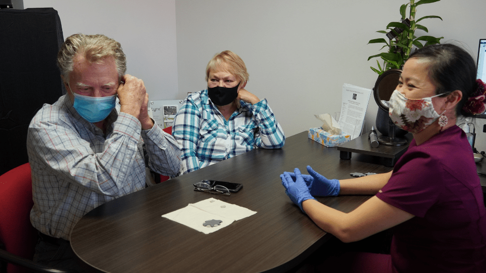 Male patient sat with wife and hearing aid specialist fitting his own hearing aid