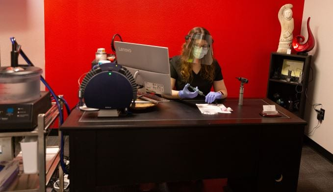 audiologist at desk wearing face mask and face sheild