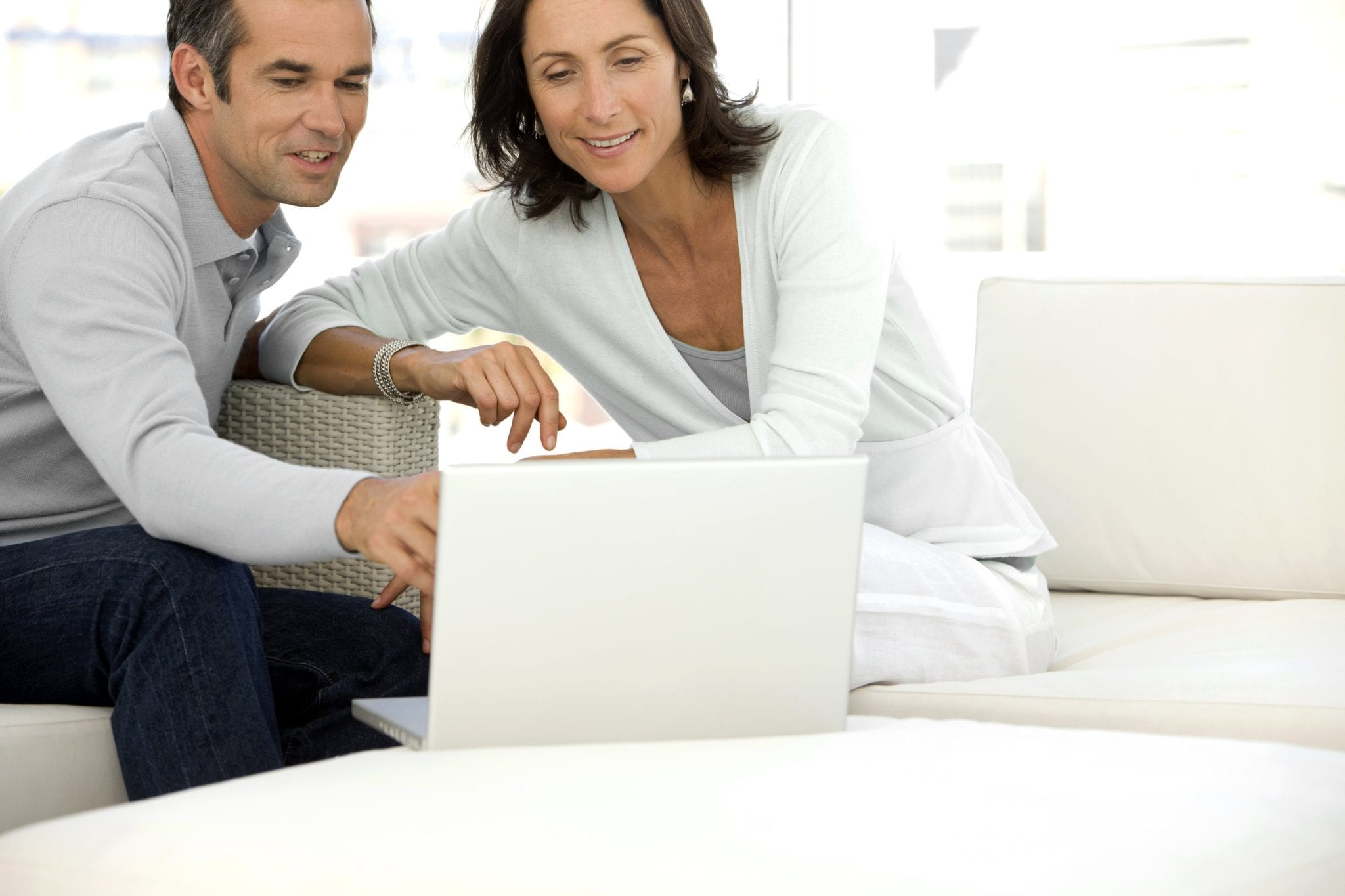 Middle-aged couple using laptop | Clarity Hearing