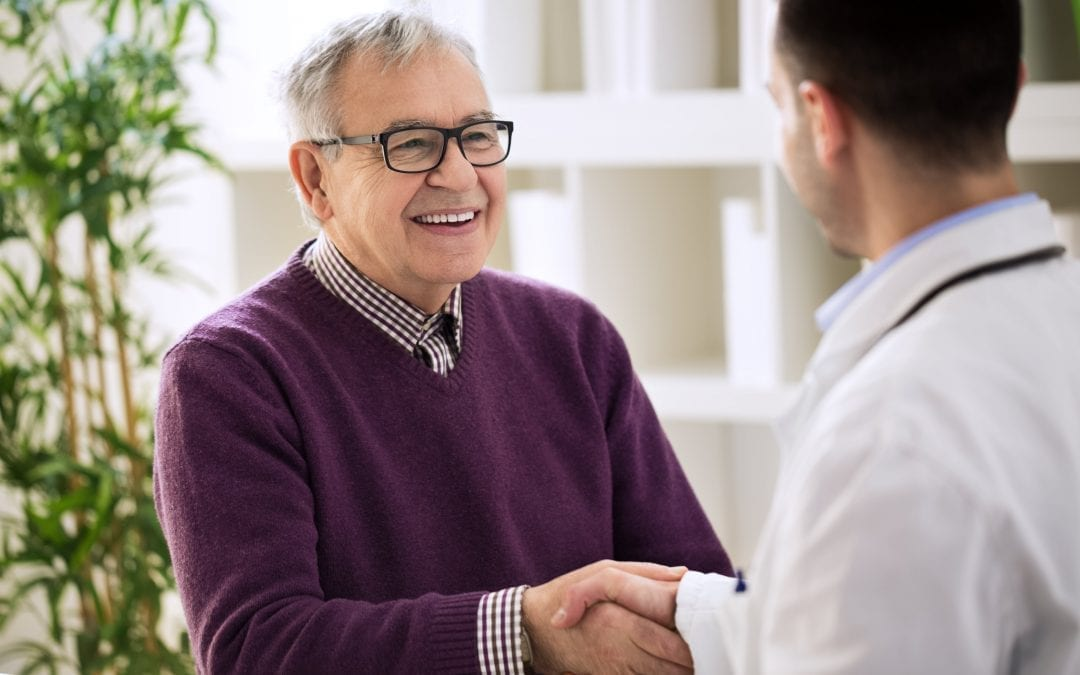 Smiling happy healthy old male shaking with doctor | Clarity Hearing
