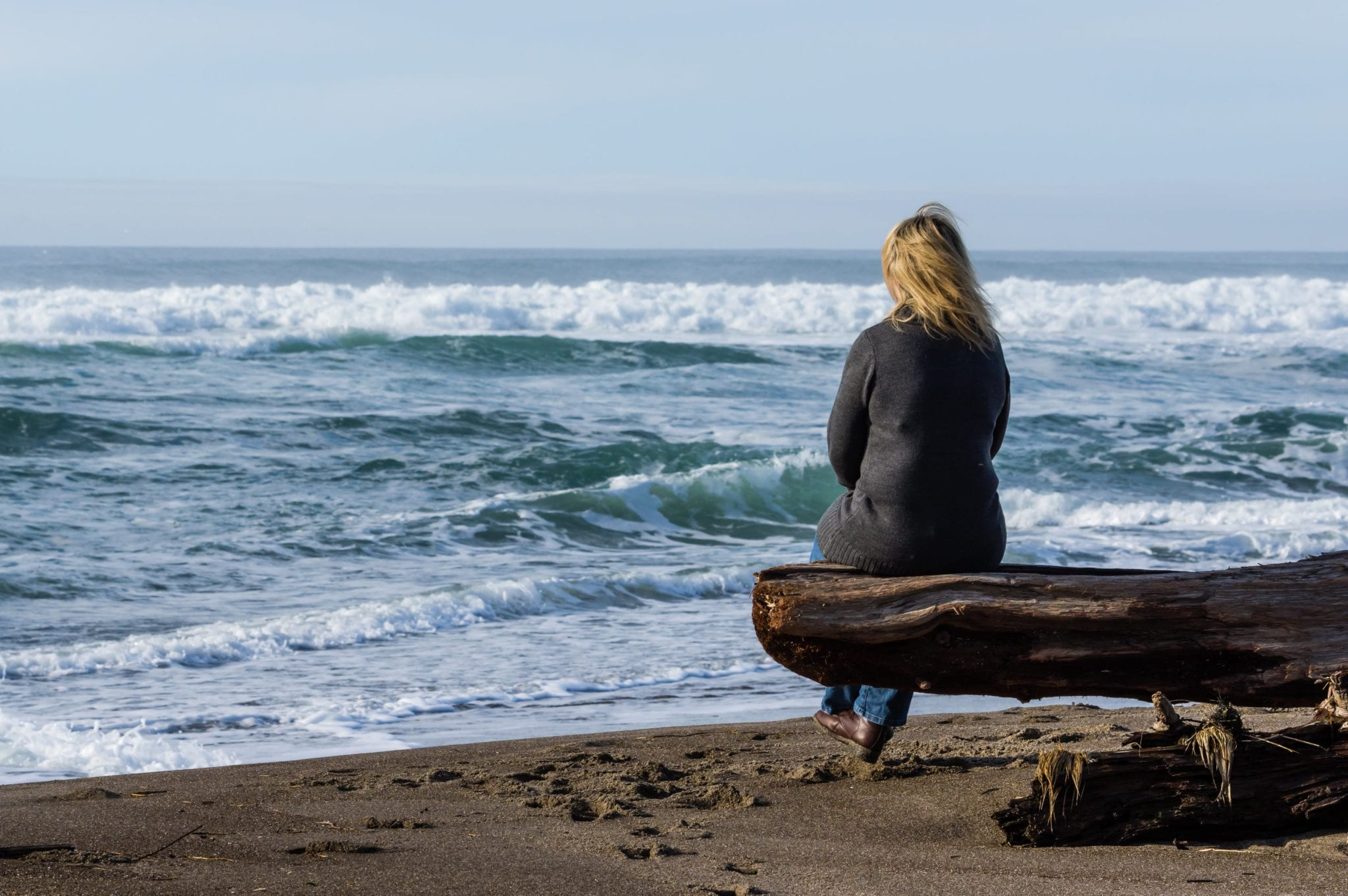 Woman sitting on a driftwood log | Clarity Hearing
