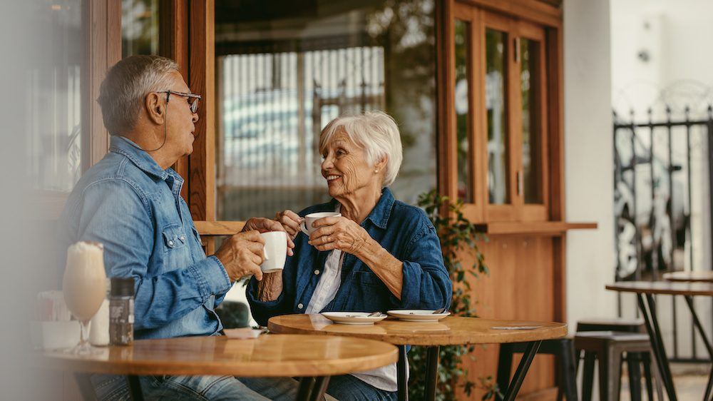 Senior couple talking over a cup of coffee at cafe | Clarity Hearing
