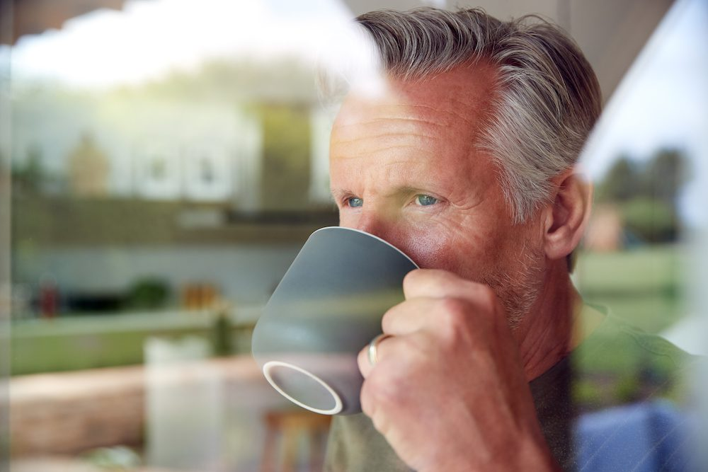 Senior Man Standing And Looking Out Of Kitchen Door Drinking Coffee Viewed Through Window | Clarity Hearing